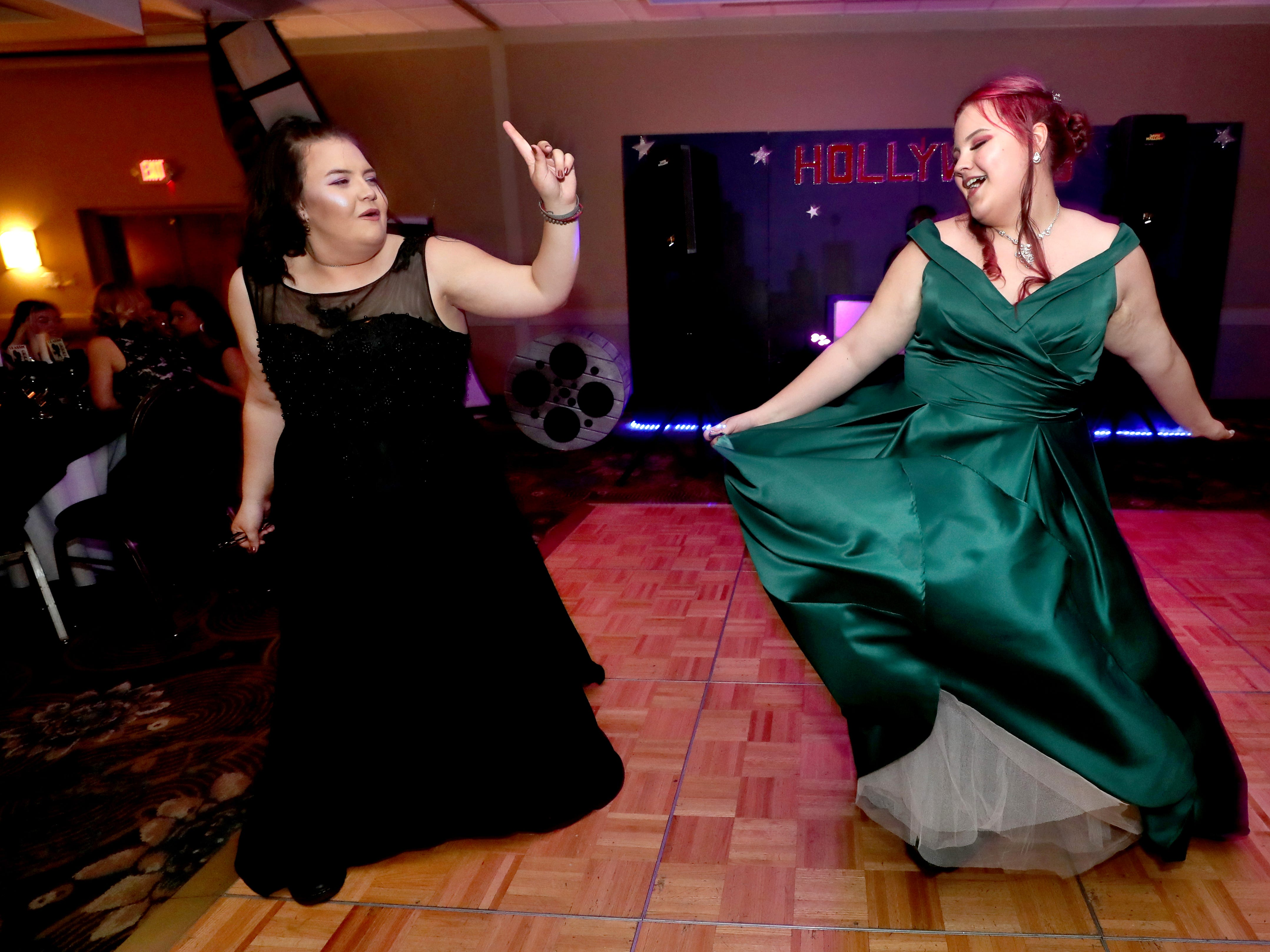 Tina Jernigan, left and Evie Douglas, right dance on the dance floor at Holloway's prom at the DoubleTree on Thursday April 18, 2019.