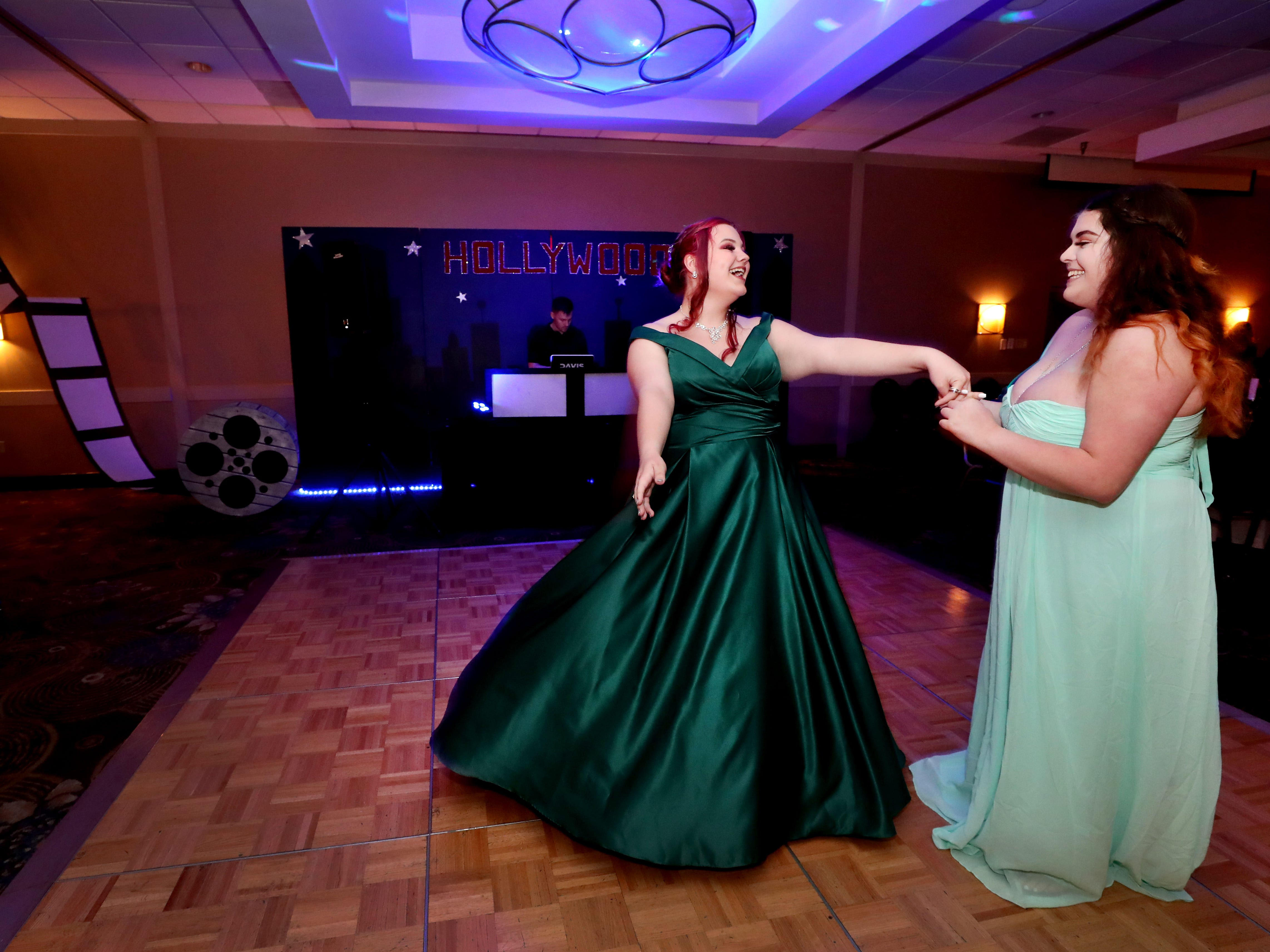 Evie Douglas and Somer Davis twirl on the dance floor at Holloway's prom at the DoubleTree on Thursday April 18, 2019.