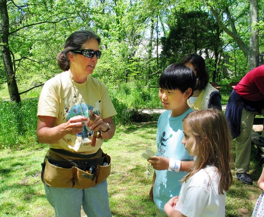 Sandy Bivens, left, shares nature tips with children at the City Nature Challenge & Spring Nature Celebration.