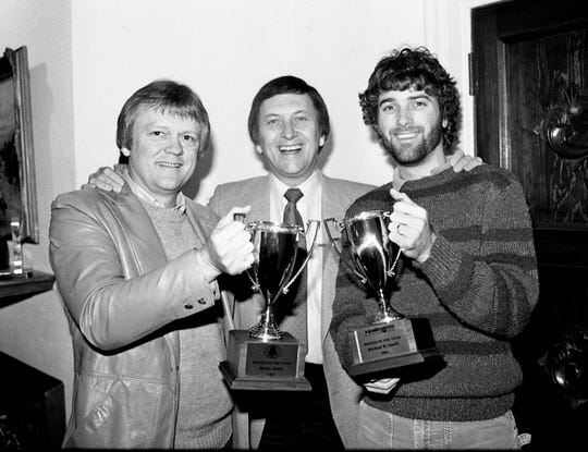 """Tree International Publishing President Buddy Killen, center, wishes two of his top songwriters """"Merry Christmas"""" by presenting them with cups for their achievements during 1984. Bucky Jones, left, and Michael W. Smith were among the dozens of Tree tunesmiths honored at the firm's annual Christmas brunch at Hillwood Country Club on Dec. 5, 1984."""