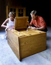 Debbie Smith and her husband, Michael W. Smith, look over a cupboard Aug. 9, 2001, that they are donating to the Heritage Foundation for its annual fundraiser, Preservation Market Place. Debbie Smith is co-chair of the event.