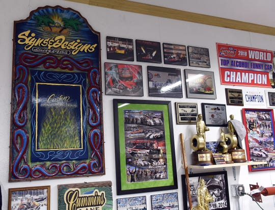 A sign for one of Steve Prince's custom painting businesses on display with racing memorabilia in his Hebron garage.