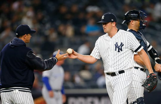 Apr 18, 2019; Bronx, NY, USA;  New York Yankees manager Aaron Boone (left) takes the ball from relief pitcher Jonathan Holder (56) in the seventh inning against the Kansas City Royals  at Yankee Stadium.