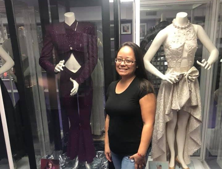 Irma Arevalo stands in front of some of Selena's most iconic looks at the Selena Museum in Corpus Christi, Texas.