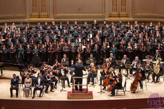The Oñate High School Choir wearing robes with teal stoles, performing at Carnegie Hall with a few other ensembles on April 8.