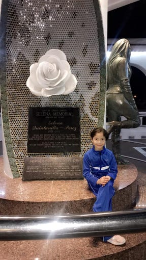 Rubi M. Garcia, 7, sits in front of Selena's memorial and statue in Corpus Christi, Texas.