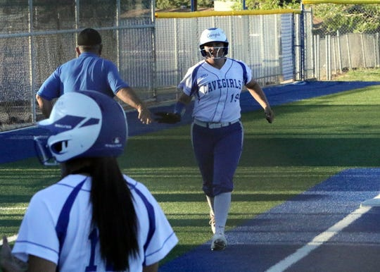 Taighen Whitzel low-fives coach John Tiggert as she trots home to celebrate her two-run homer against Roswell on April 18, 2019. Whitzel finished the season with three home runs and a .441 batting average.