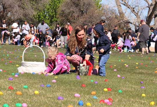 A family collects eggs, Friday, April 19, 2019, during the Easter EGGStravaganza at Sycamore Park.