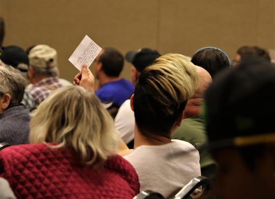 An audience member holds up a card with a question written on it Thursday during a community forum at the Farmington Civic Center.