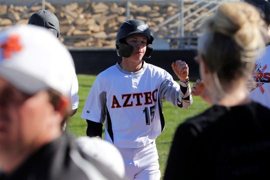 Aztec's Colton Sparks is welcomed back to the dugout after scoring a run against Gallup during Thursday's game at AHS.