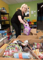 Kim Cheney, president and founder of 400 Paws, sorts pet food and items that her organization has collected on Friday. The organization will hold its first pet food distribution from 1 to 3 p.m. April 28.