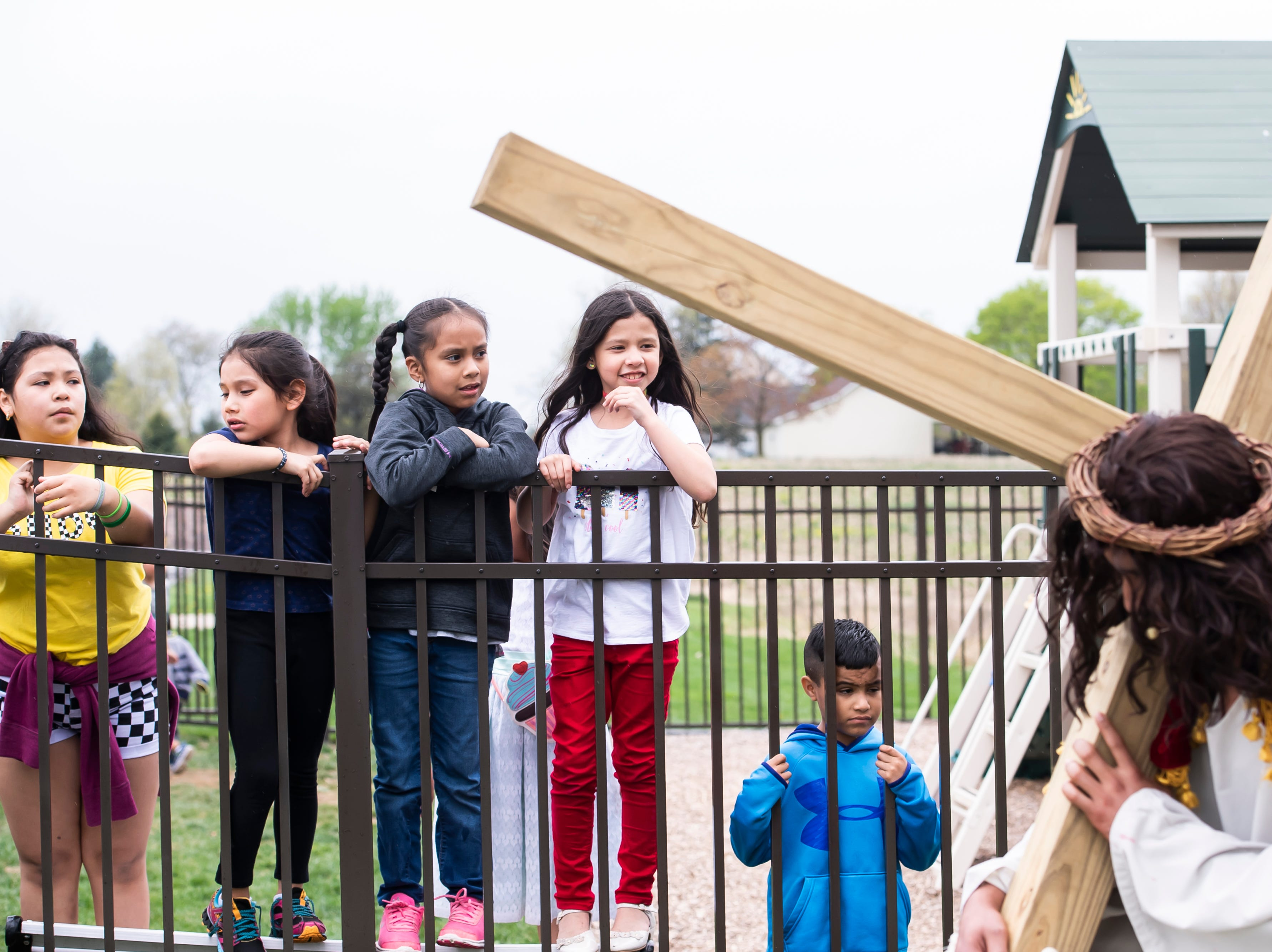 Children look on as Jesus carries his cross during St. Joseph Catholic Church's Good Friday procession on Friday, April 19, 2019.