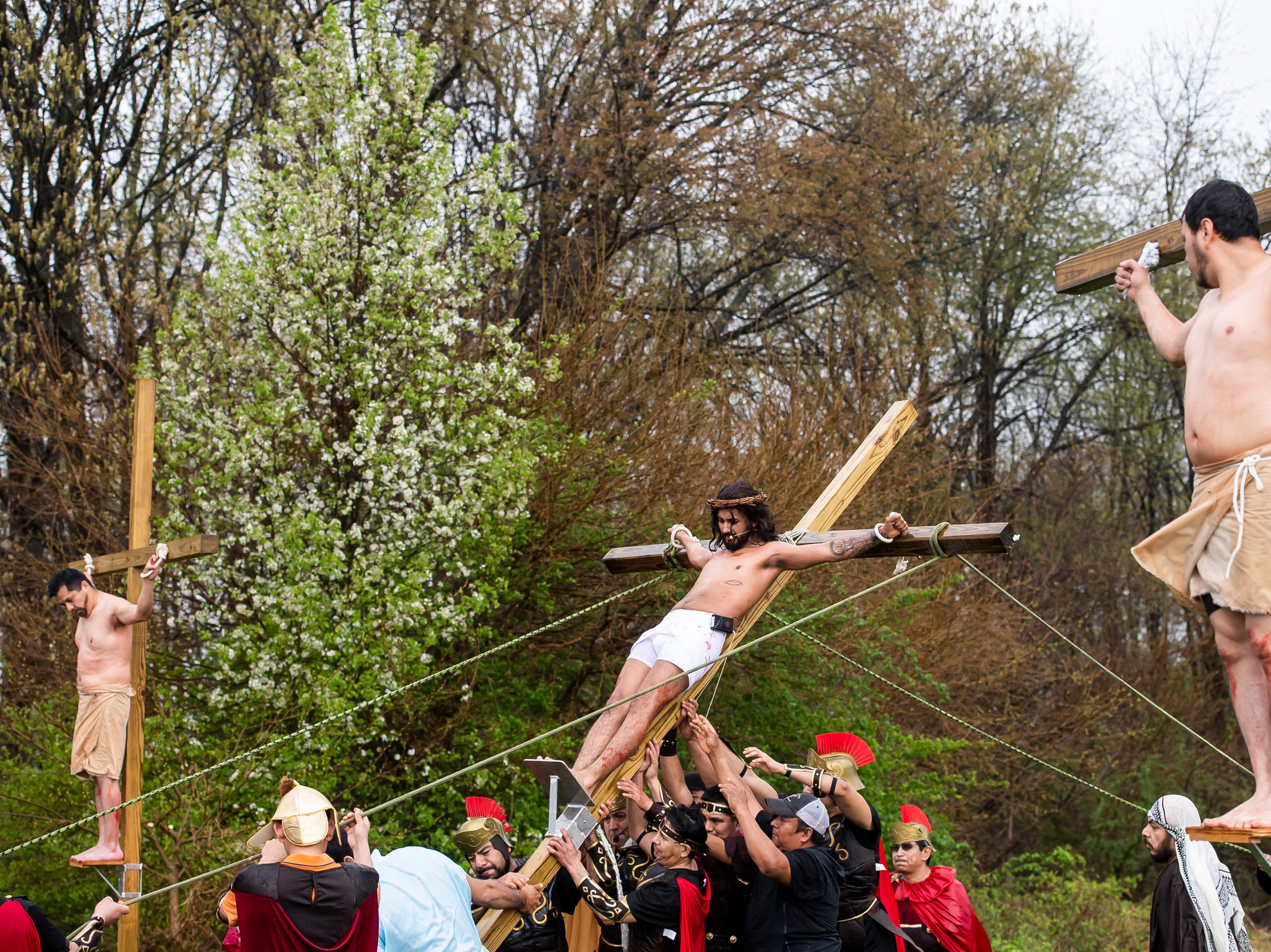 Jose Negret, portraying Jesus, has his cross lifted during a Stations of the Cross procession at St. Joseph Catholic Church in Hanover on Good Friday, April 19, 2019.