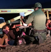 A U.S. Border Patrol agent reviews documents as some of the 30 migrants intercepted crossing the border in Yuma wait to be processed.