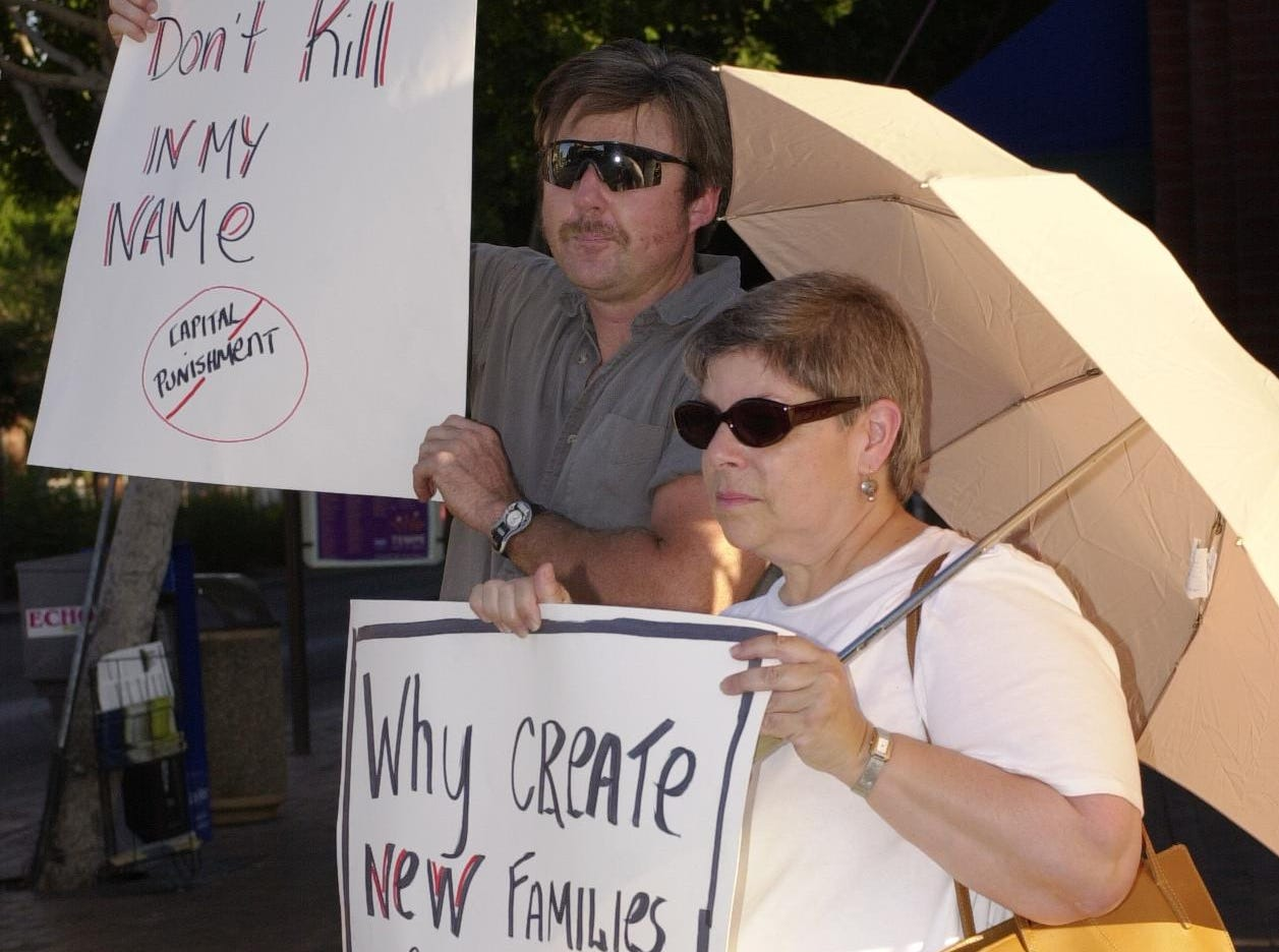 Jim Whitesell of Tempe and Eleanor Eisenberg hold signs in downtown Tempe in protest of the death penalty.  About a dozen protesters stood on the corner of 6th Ave. and Mill on the eve of Timothy McVeigh's execution.