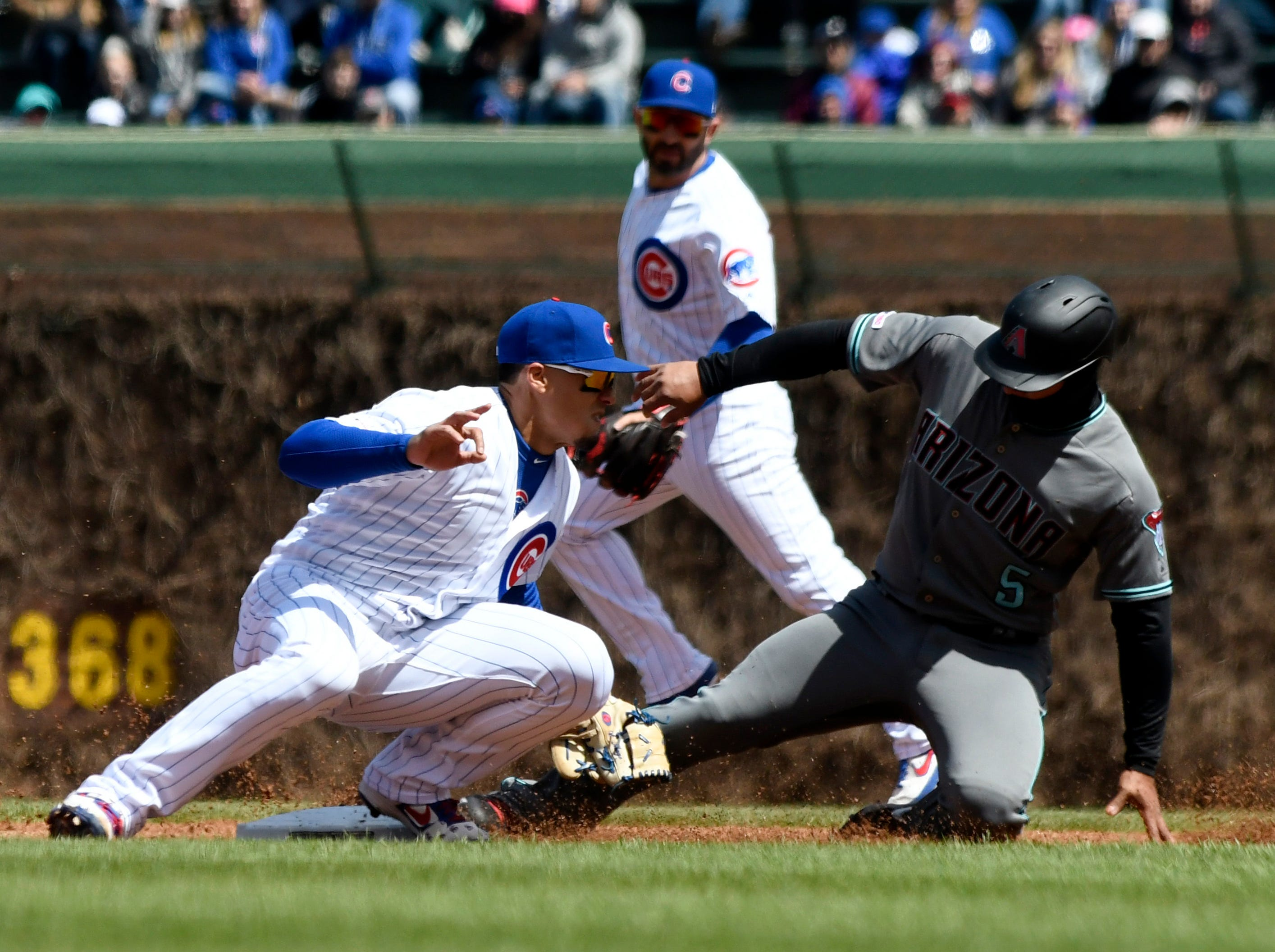 Chicago Cubs shortstop Javier Baez (9) tags out Arizona Diamondbacks' Eduardo Escobar (5) on a steal attempt at second base during the first inning of a baseball game, Friday, April 19, 2019, in Chicago. (AP Photo/David Banks)