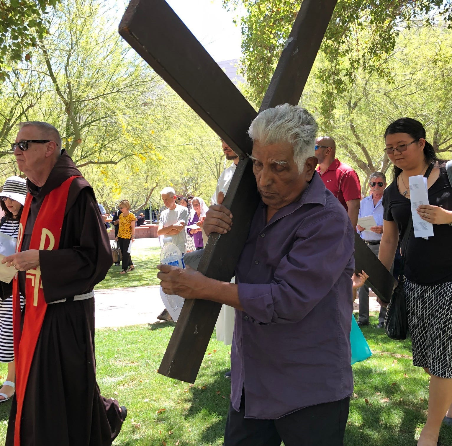Tommy Almanza carries the cross at St. Mary's Roman Catholic Basilica on Friday.