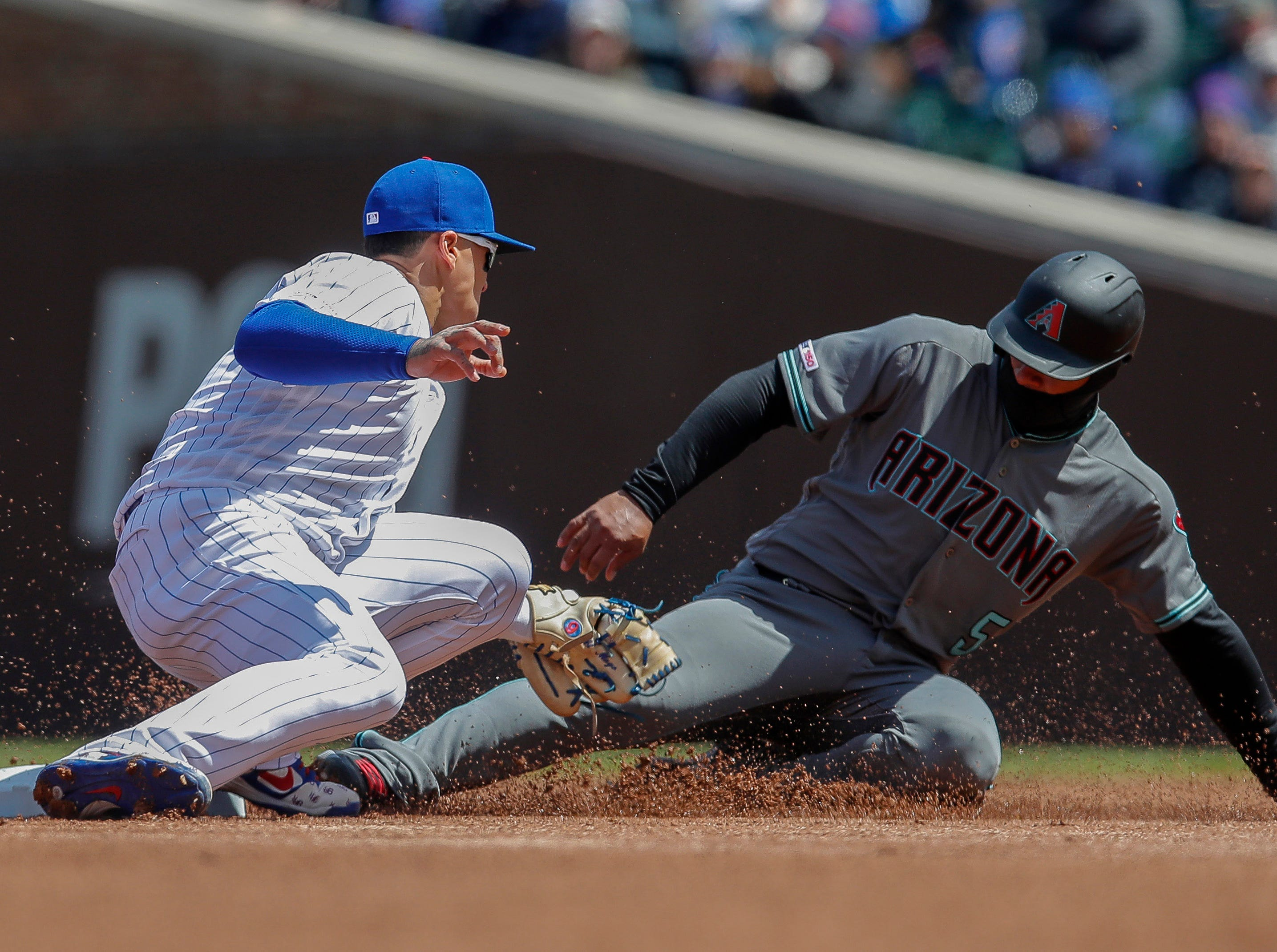 Diamondbacks third baseman Eduardo Escobar is tagged out by Cubs shortstop Javier Baez as he tries to steal second base during the first inning of a game April 19 at Wrigley Field.