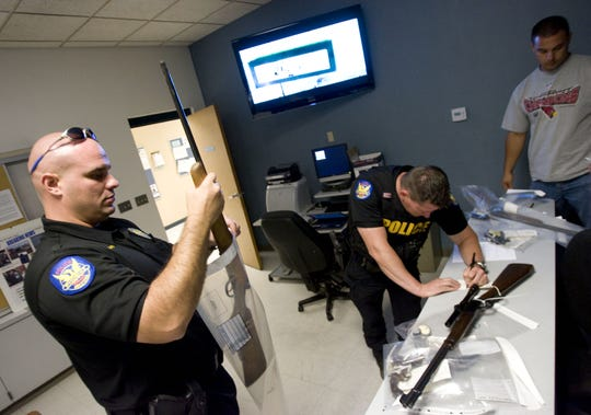 Phoenix Police Officer Tim Baiardi (left) impounds a firearm that was surrendered at the Phoenix Police Department Maryvale precinct on Sat., June 13, 2009.