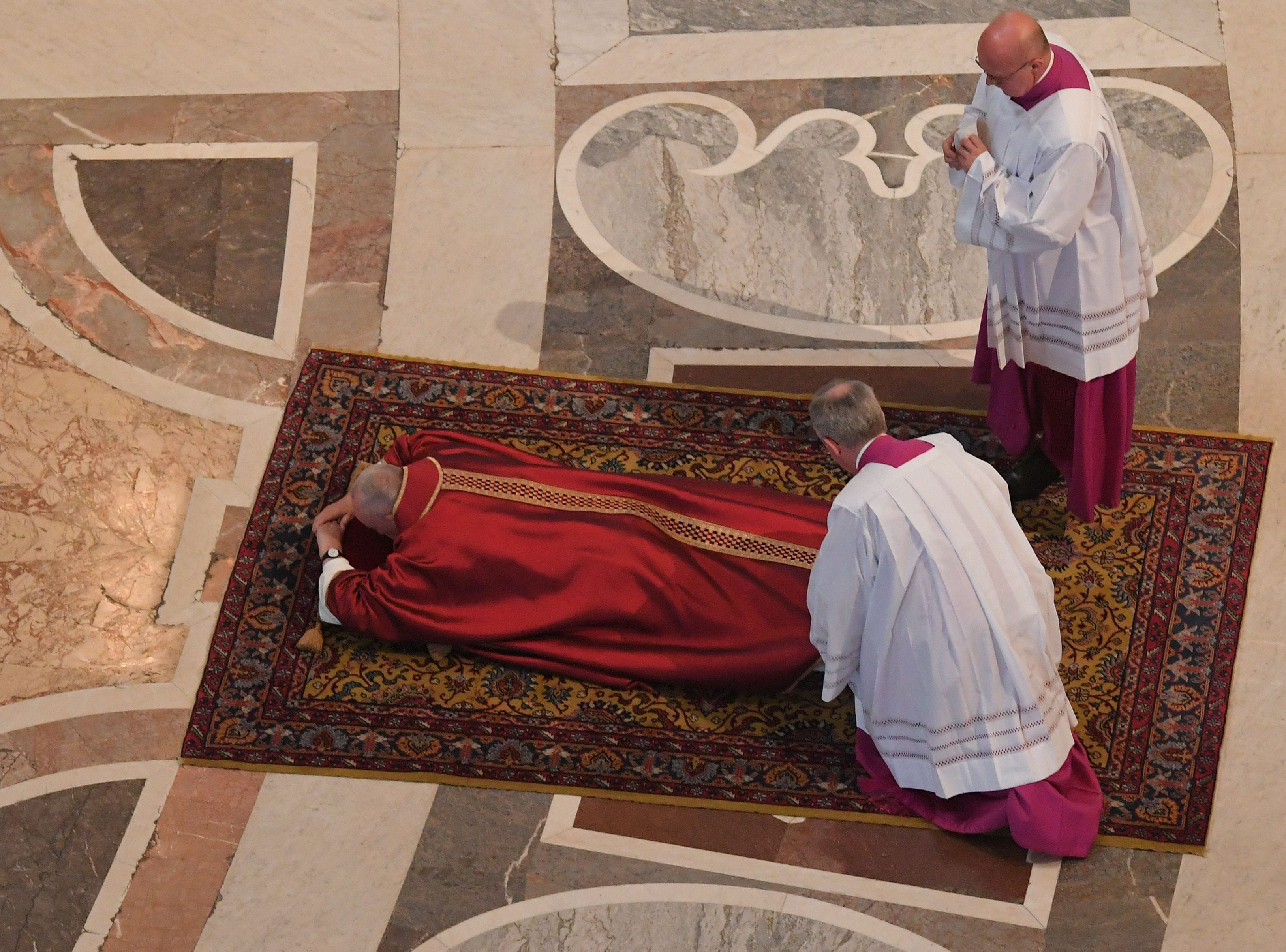 Papal Master of Ceremonies, Monsignor Guido Marini (R) arranges Pope Francis' cloth as the Pope prays during the Celebration of the Lord's Passion on Good Friday at St Peter's Basilica, on April 19, 2019 in the Vatican. - Christians around the world are marking the Holy Week, commemorating the crucifixion of Jesus Christ, leading up to his resurrection on Easter. (Photo by Tiziana FABI / AFP)        (Photo credit should read TIZIANA FABI/AFP/Getty Images)