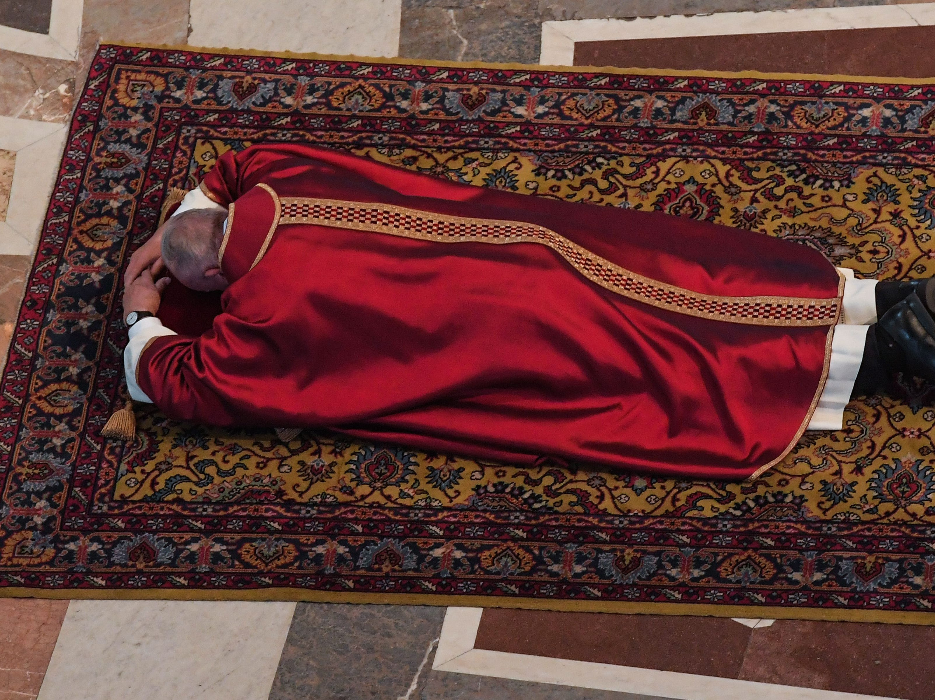 Pope Francis lies on the ground to pray during the Celebration of the Lord's Passion on Good Friday at St Peter's Basilica, on April 19, 2019 in the Vatican. - Christians around the world are marking the Holy Week, commemorating the crucifixion of Jesus Christ, leading up to his resurrection on Easter. (Photo by Tiziana FABI / POOL / AFP)        (Photo credit should read TIZIANA FABI/AFP/Getty Images)