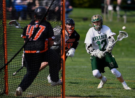 Chandler Hake shoots for a York Catholic goal against York Suburban, Thursday, April 18, 2019.