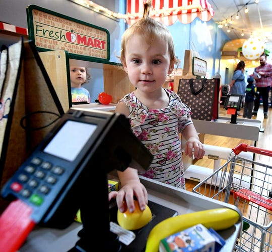 Marley Ruby, 2, of Shiloh, grocery shops with her friend Meadow Stough, 3, of Dover Township, left, while they play in the market at The Curious Little Playhouse, the new business at 41 W. Market St. in York City Friday, April 19, 2019. The interactive childrenÕs play place offers a variety of stations for kids. Jen Swanner is the owner of the business which staged a ribbon cutting earlier in the day. Bill Kalina photo