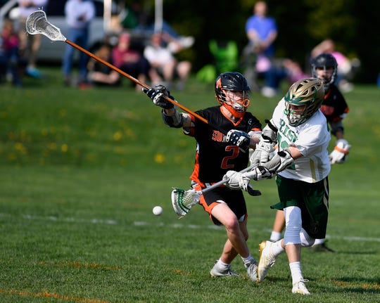 Chandler Hake of York Catholic shoots around Joe Shearer of York Suburban for a goal, Thursday, April 18, 2019.