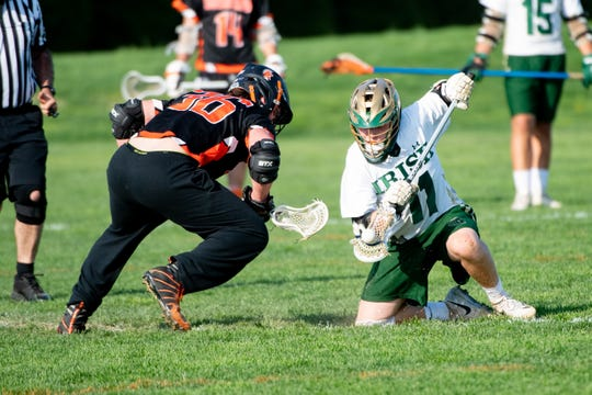 Drew Snelbaker (11) wins the face-off during the boys' lacrosse game between York Catholic and York Suburban, April 18, 2019 at York Catholic High School. The Fighting Irish defeated the Trojans 22 to 3.