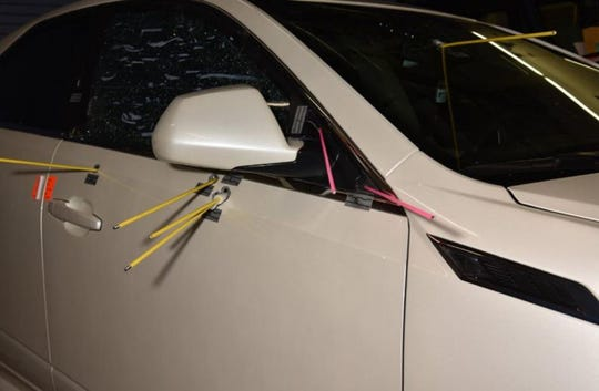 A photo showing bullet holes in the suspect vehicle.