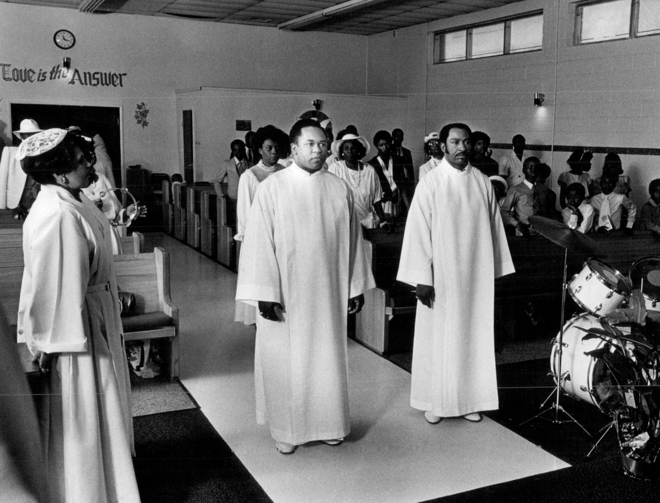 Minister Glenn King and church member Flodell Richardson proceed to the altar of First Church Divine as Easter Service begins in this 1985 photo.