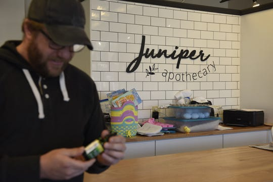Joshua Sopko, co-founder of Juniper Apothecary, holds a bottle of CBD oil, available for purchase at the storefront at 401 E. Eighth St.  Juniper received its first shipment of SUNSoil CBD oil products about two weeks ago.