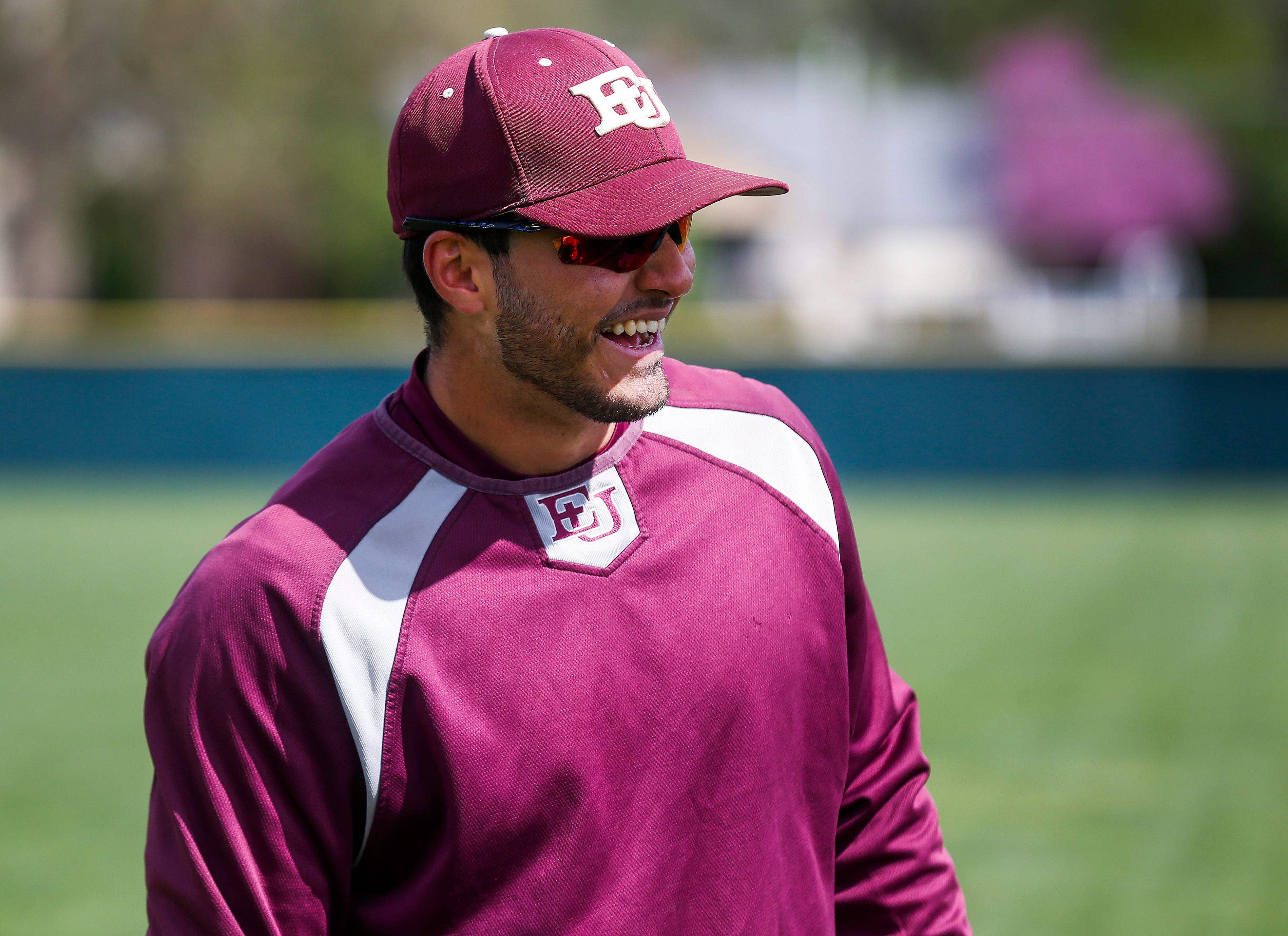 Jose Vargas, a shortstop at Evangel University, laughs with teammates before a double-header on Friday, April 19, 2019. Vargas, a senior, is stuck in limbo because of what is happening in his home country of Venezuela.