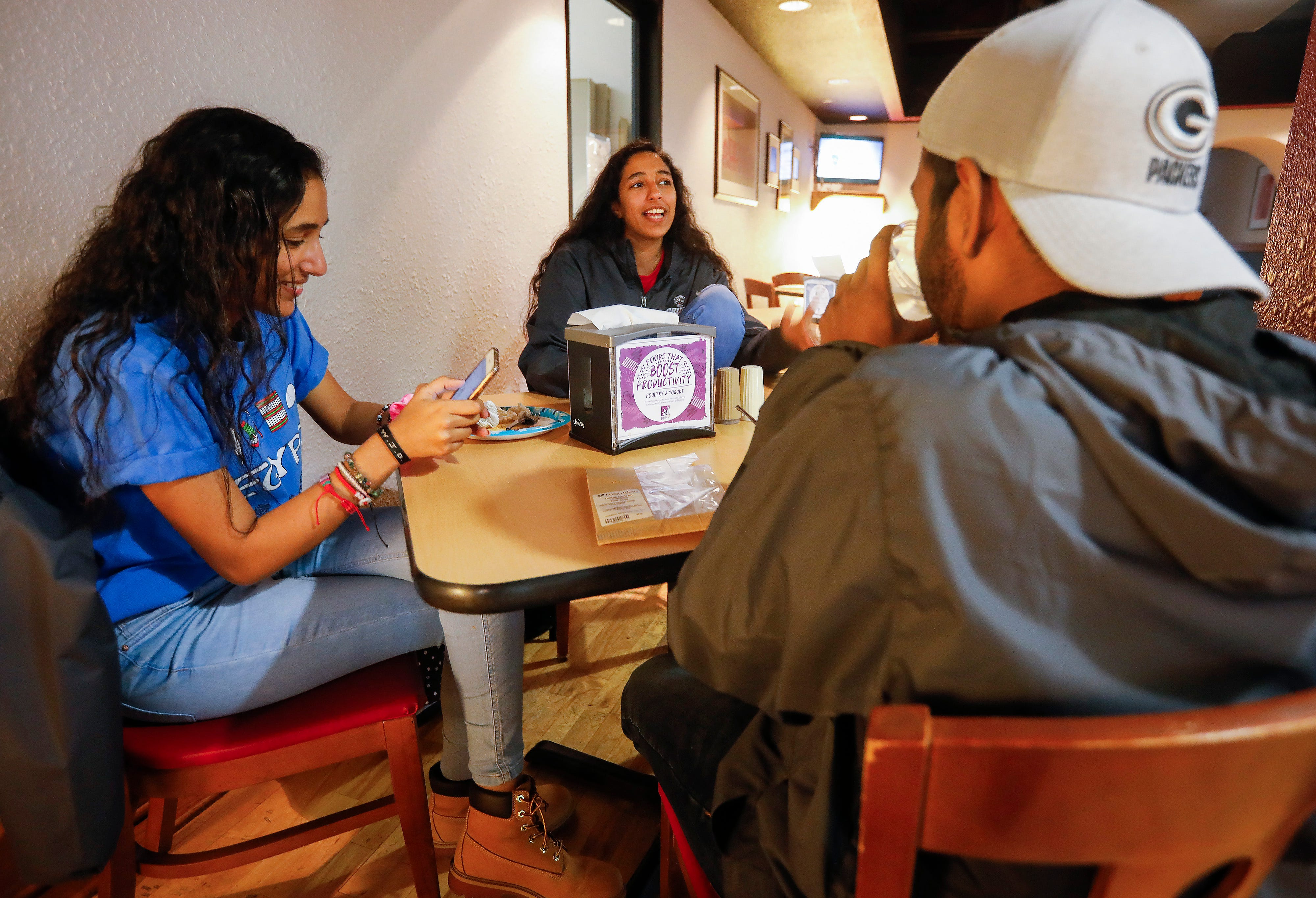 Velona, center, and Verna Tawfik, twin sisters from Egypt who are juniors at Drury University, eat lunch with their friend Naviinesh Gunalan on Thursday, April 18, 2019.