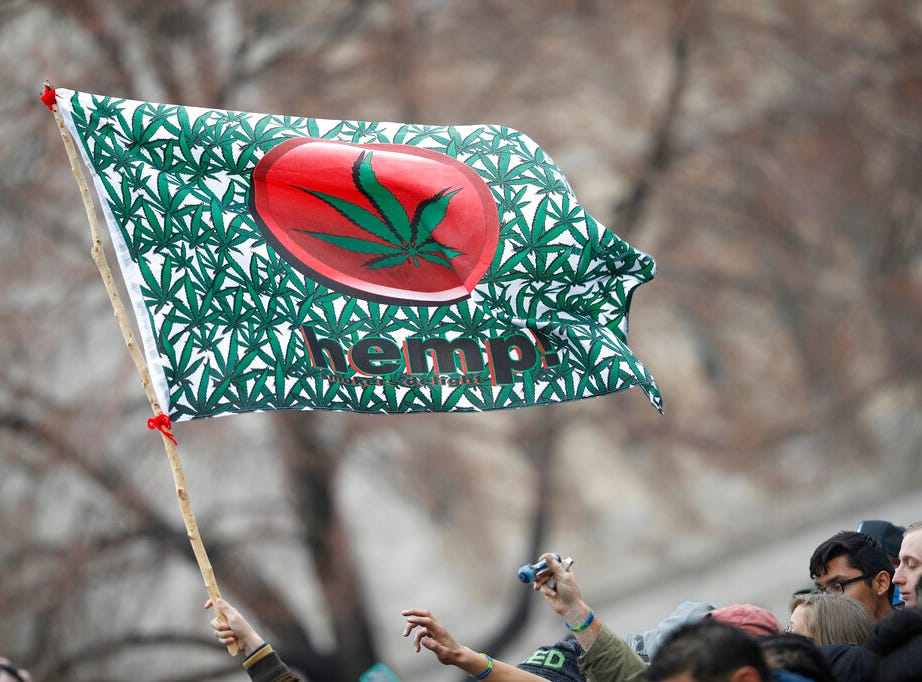 FILE - In this April 20, 2018 file photo an attendee hoists a flag during the Mile High 420 Festival in Denver. Potheads have for decades celebrated their love of marijuana on April 20, but the once counter-culture celebration that was all about getting stoned now is so mainstream Corporate America is starting to embrace it. (AP Photo/David Zalubowski, File)