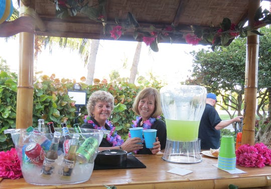 Volunteers Lisa Arnold, left, and Cara Vietri enjoy a Bahamian libation  at the ribbon cutting ceremony for phase one of the $32 million Believe Capital Campaign at Maltz Jupiter Theatre.