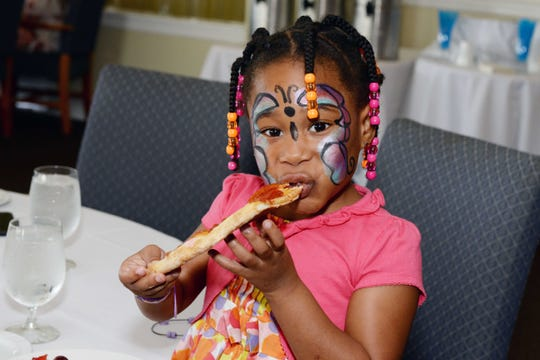 Chloe Daniels enjoys a slice of pizza from the kid-friendly buffet at the father/daughter dance hosted by Grace Way Village at Pelican Yacht Club in Fort Pierce.