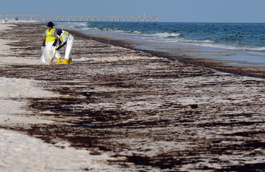 In a June 23, 2010 file photo, crews work to clean up oil from the Deepwater Horizon oil spill washed ashore at Pensacola Beach in Pensacola Fla.