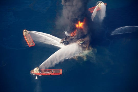 In this April 21, 2010, file photo, the Deepwater Horizon oil rig burns in the Gulf of Mexico following an explosion that killed 11 workers and caused the worst offshore oil spill in the nation's history. President Donald Trump is throwing out a policy devised by his predecessor for protecting U.S. oceans and the Great Lakes, replacing it with a new approach that emphasizes use of the waters to promote economic growth. President Barack Obama issued his policy in 2010 after the Deepwater Horizon oil spill in the Gulf of Mexico. Trump says it was too bureaucratic.