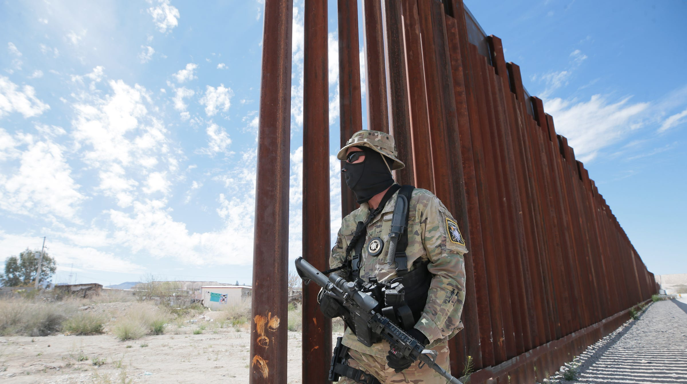 """""""Viper,"""" A member of the United Constitutional Patriots-New Mexico Border Ops, stands where the bollard fence in Anapra, New Mexico ends. The group has been camped out on the border for a few months helping Border Patrol watch this section of border."""