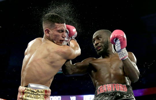 In this Oct. 13, 2018, file photo, Terence Crawford, right, connects with Jose Benavidez during their WBO welterweight title boxing bout in Omaha, Neb. Crawford (34-0, 25 KOs) defends his welterweight title at Madison Square Garden on Saturday, April 20, 2019, against veteran Amir Khan (33-4, 20 KOs), the 2004 Olympic silver medalist from Britain who 15 years later is looking for what could be his biggest victory as a professional.