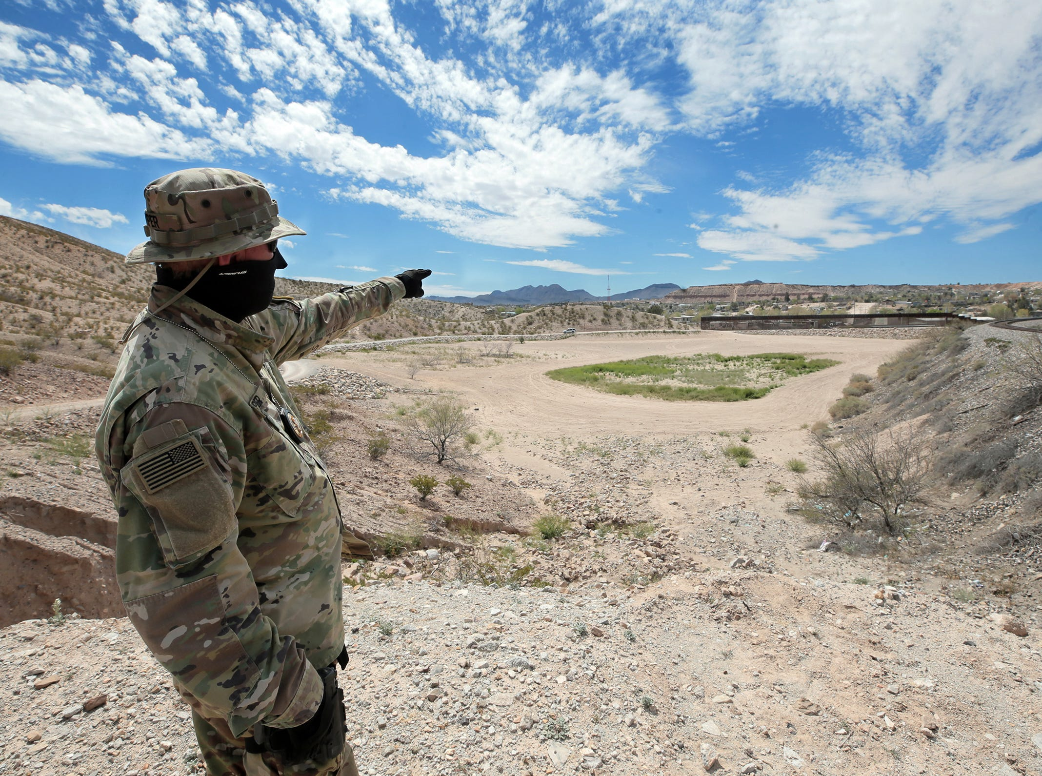 """Viper,"" A member of the United Constitutional Patriots-New Mexico Border Ops, points to where the bollard fence in Anapra, New Mexico ends, a point they say is a weak spot."