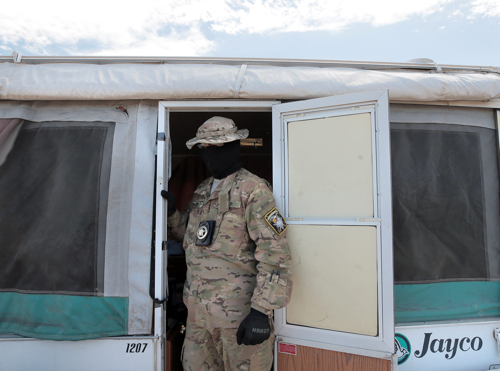 "A United Constitutional Patriot who goes by ""Stinger"" prepares to leave one of the camp's trailers for a patrol along the border in Anapra, New Mexico."