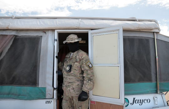 """A United Constitutional Patriot who goes by """"Stinger"""" prepares to leave one of the camp's trailers for a patrol along the border in Anapra, New Mexico."""