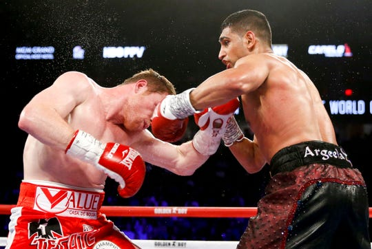 In this May 7, 2016, file photo, Canelo Alvarez, left, is hit by Amir Khan during their WBC middleweight title fight in Las Vegas. Terence Crawford (34-0, 25 KOs) defends his welterweight title at Madison Square Garden on Saturday, April 20, 2019, against veteran Khan (33-4, 20 KOs), the 2004 Olympic silver medalist from Britain who 15 years later is looking for what could be his biggest victory as a professional.