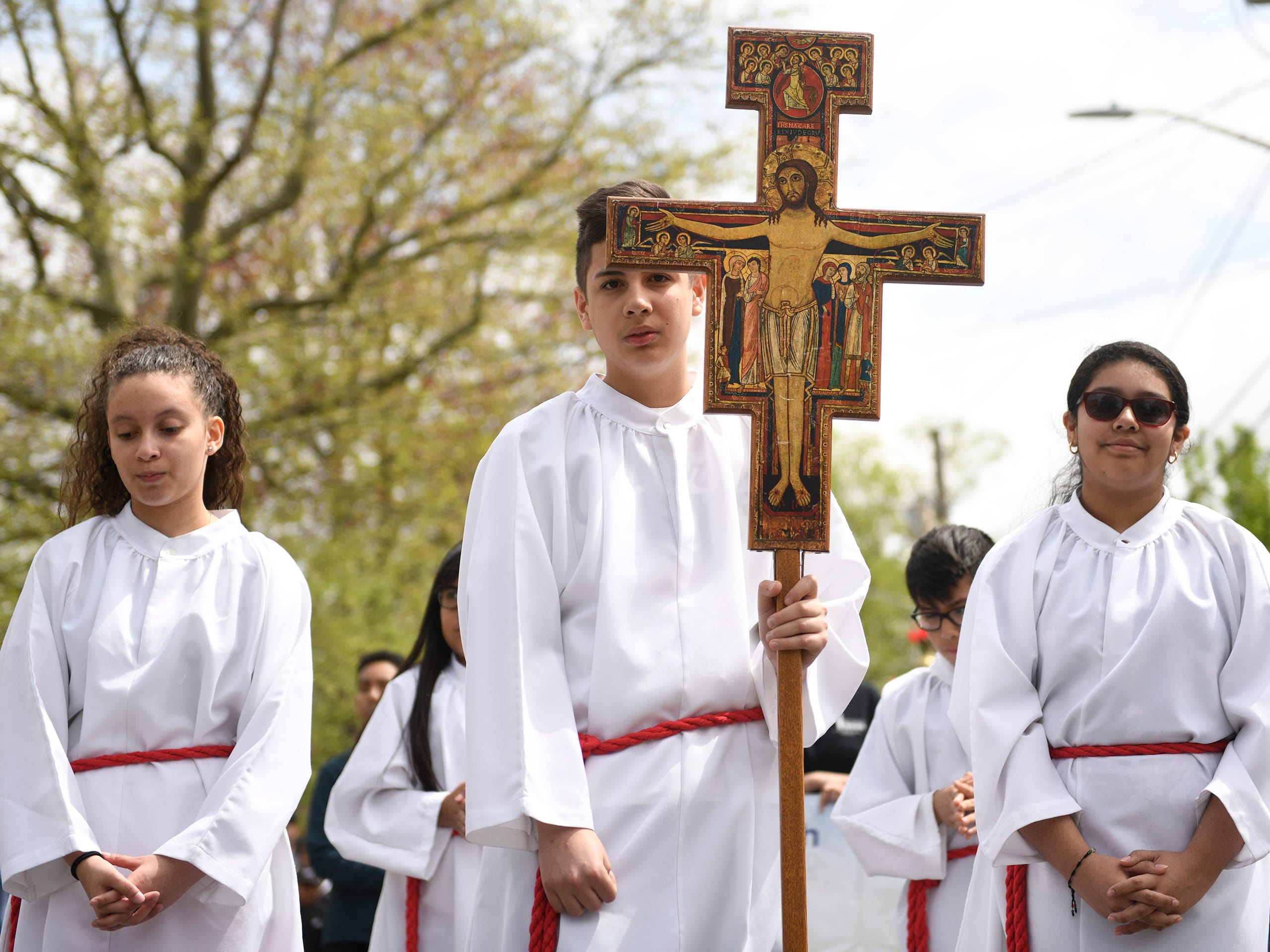 Betzalis DeLaCruz, Angel Munier and Donna Salazar participated in leading the Good Friday procession down Almond Street on Friday, April 19.