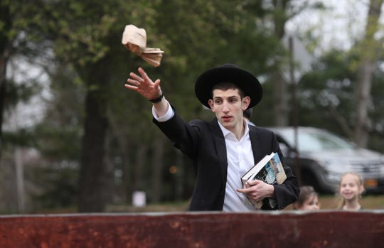 Josheph Nussbaum, 19, from Wesley Hills as throws leavened bread products into the fire at Manny Weldler Park in Ramapo on Friday, April 19, 2019 before the start of Passover.