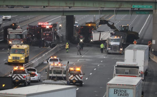 Workers clean-up debris after a tractor trailer rolled over on the New York State Thruway in Yonkers, April 19, 2019.