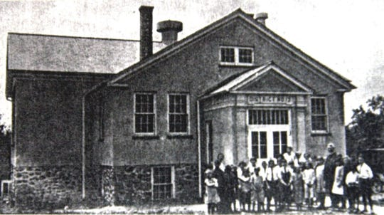 Students pose outside Camp Hill School, with the Rev. William Briscoe, in 1927. The building is now used as the Pomona Village Hall.