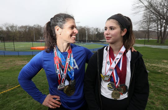 Kim Lindner, 47, of Chappaqua and her daughter Kira, 16, a Horace Greeley junior, with their medals in track and field throwing, at the high school April 18, 2019. Twenty years after throwing in college, Kim returned to throwing the shot and discus after 10-year-old Kira expressed interest. The two have gone on to marked success.